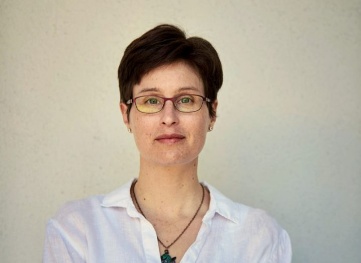 View of woman with short cropped hair and white shirt and glasses looking at camera.