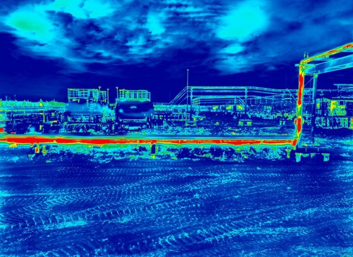 Infrared thermal imaging of industrial pipes glowing red with heat.