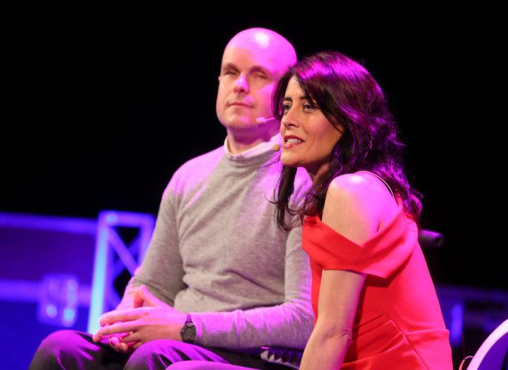 A bald man in a soft grey jumper is seated next to a dark-haired woman in a red top. Both are wearing head mics.