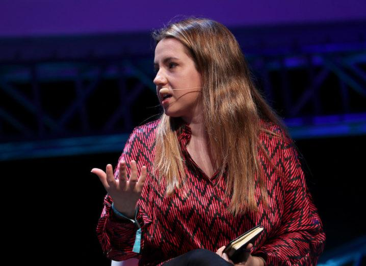 A woman in a red chevron-printed shirt is seated on stage wearing a head-mic and holding a notebook as she speaks to someone on her right.