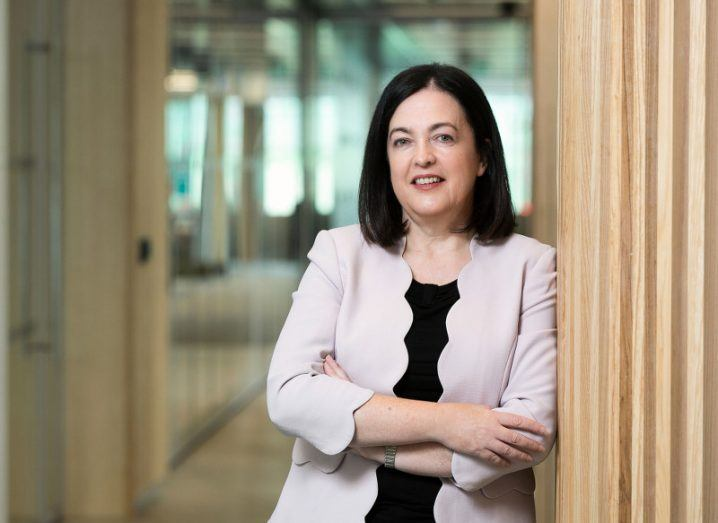 Jacky Fox wears a light scallop-edged blazer, standing with her arms crossed, leaning against a wooden wall in a hallway at Accenture's Dublin office.
