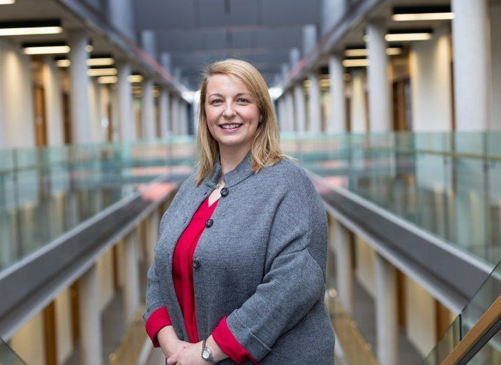 Joanne Masterson smiling in a grey cardigan in a hallway at Maynooth University.
