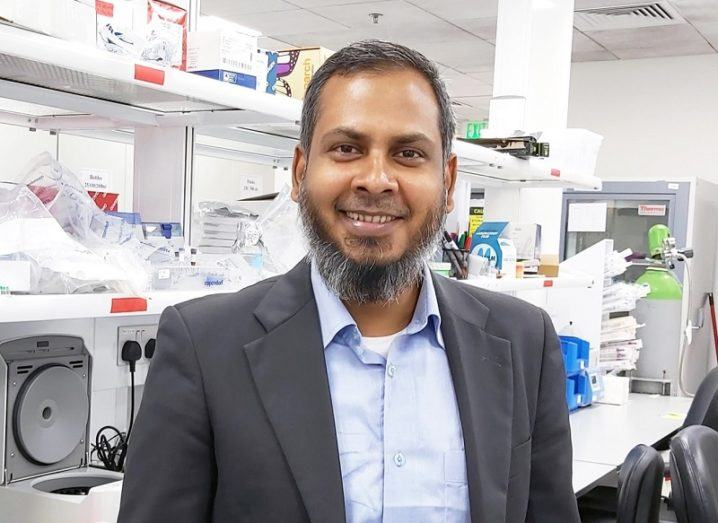 Dr Kabir H Biswas smiling in a grey blazer and blue shirt in his lab.