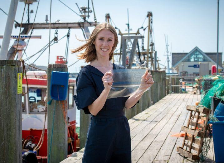 Lucy Hughes smiling on a fishing boat dock holding a MarinaTex plastic sheet.