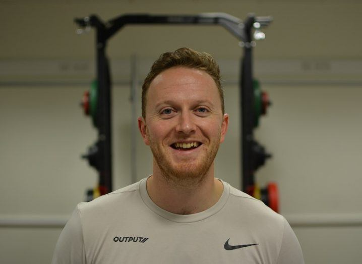 A man in a beige T-shirt with a black Nike logo smiles into the camera in front of a rack of weights in a gym. He has auburn hair and some stubble.
