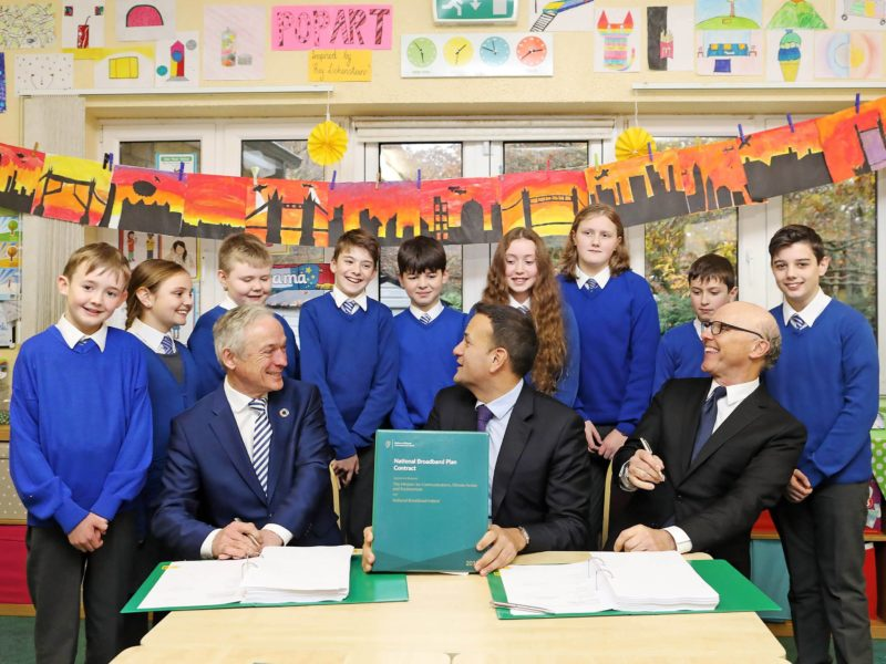 Richard Bruton, Leo Varadkar and David McCourt sitting at a table in a school with a group of children in uniforms behind them. On the table is a copy of the National Broadband Plan.