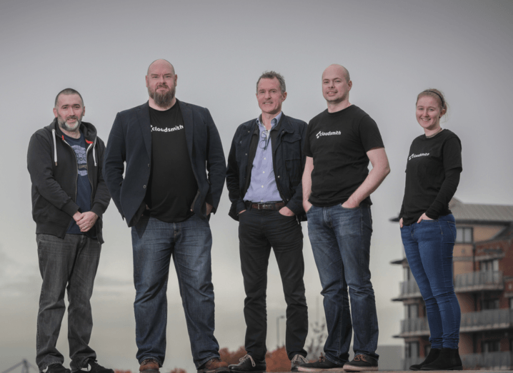 A group of five Cloudsmith employees stand in front of a grey sky in Belfast, all wearing black T-shirts with the white Cloudsmith logo on the front.