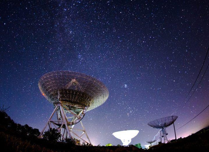 Fisheye lens shot of radio telescopes pointed at the Milky Way at night.