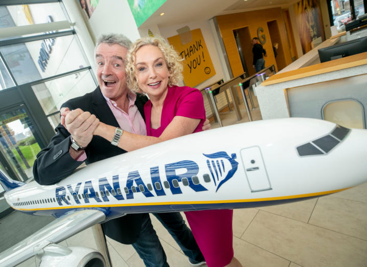A man in a black suit jacket, blue jeans and a pink shirt, with grey hair, smiles as he holds hands with a woman in a pink dress with short, blonde, curly hair. They are standing behind a large model Ryanair airplane, in the lobby of Ryanair's office in Swords, Co Dublin. The lobby has a beige tiled floor and a large window on the wall.