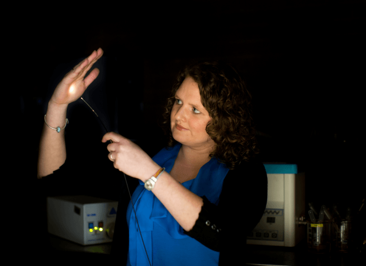 A woman with brown, curly hair stands in a dark room holding an optical fibre cable in the air with one hand, shining the light from it into the palm of the other hand. She is wearing a blue blouse with a black cardigan over it.