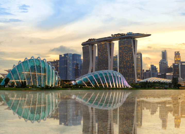 Unique skyscrapers in various shapes and sizes along the skyline of Singapore underneath a sunset. All of the buildings are reflected in a body of water.