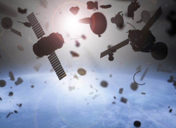 Space junk in orbit, with satellites and other materials floating above a blue planet.