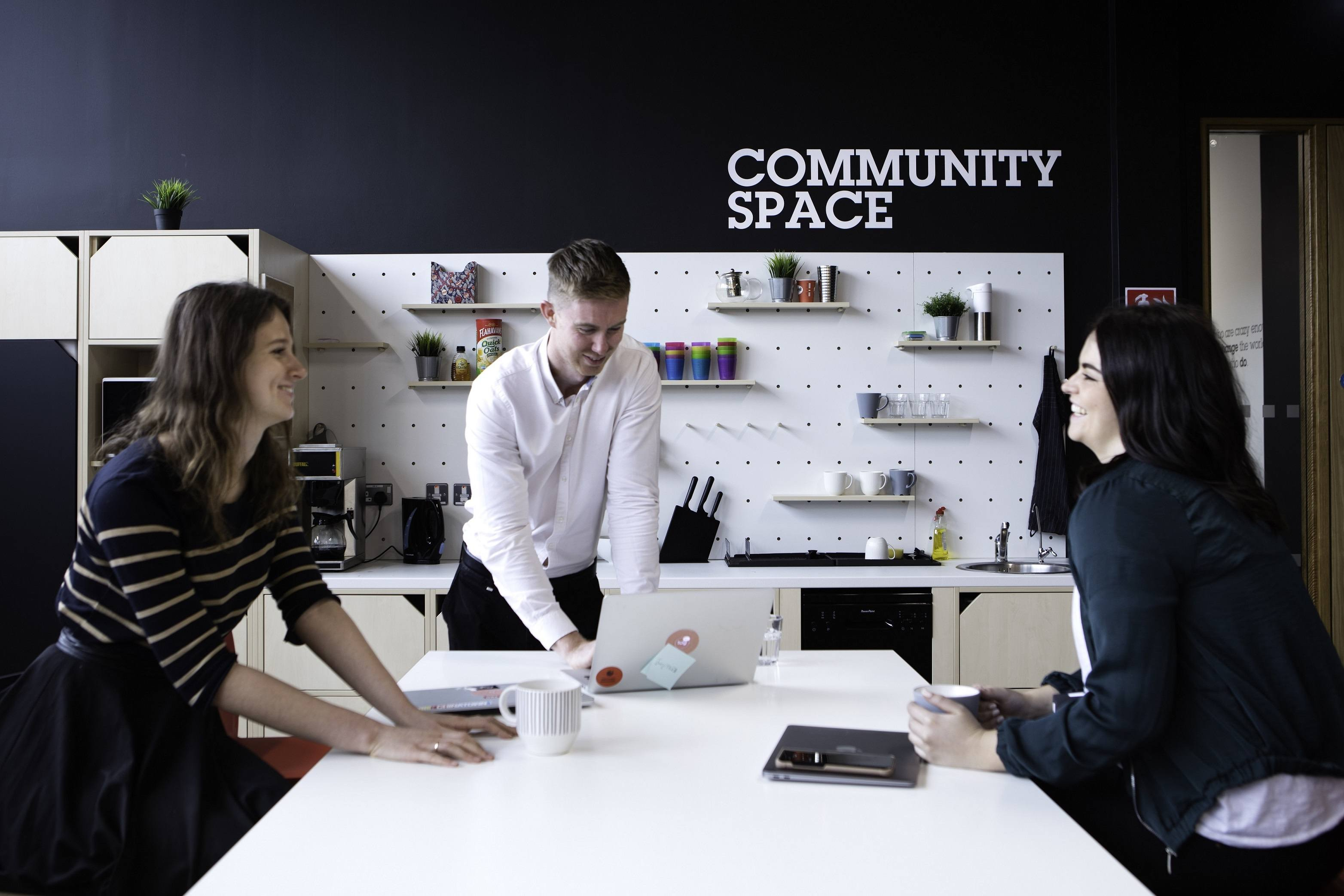A young man in a white shirt leans on a white table beside two women on either side of him. They are wearing black shirts and using laptops at a table. In the background, the wall says 'community space' on the wall.