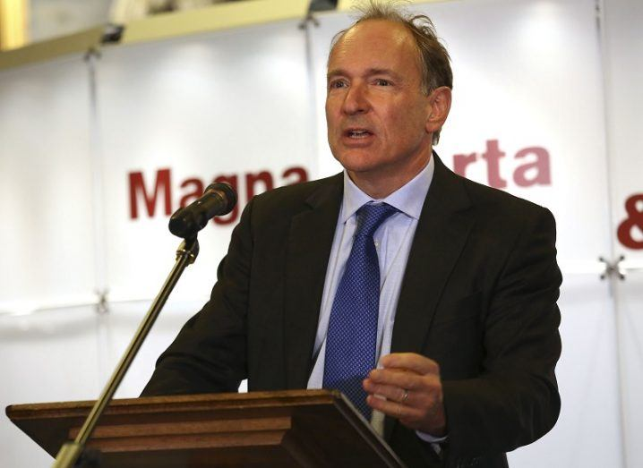 Tim Berners-Lee standing at a podium in a black blazer, purple tie and light blue shirt.