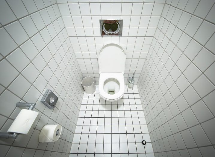 Fisheye shot of a white tiled bathroom with a white toilet in its centre.