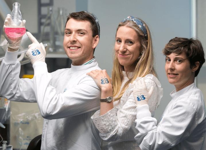 Three scientists in white lab coats with blue butterflies painted on their hands.
