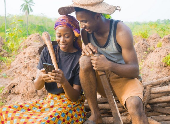 Rural African couple smiling while looking at a mobile phone.
