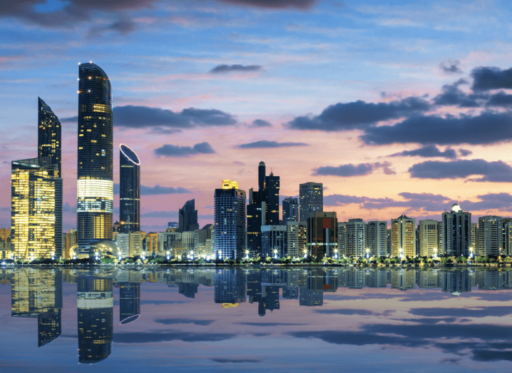 Large skyscrapers along the skyline of Abu Dhabi in front of a body of water.
