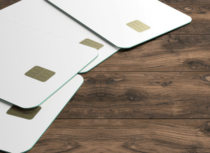 Four white credit cards which bear a resemblance to the Apple Card on a dark wooden surface.
