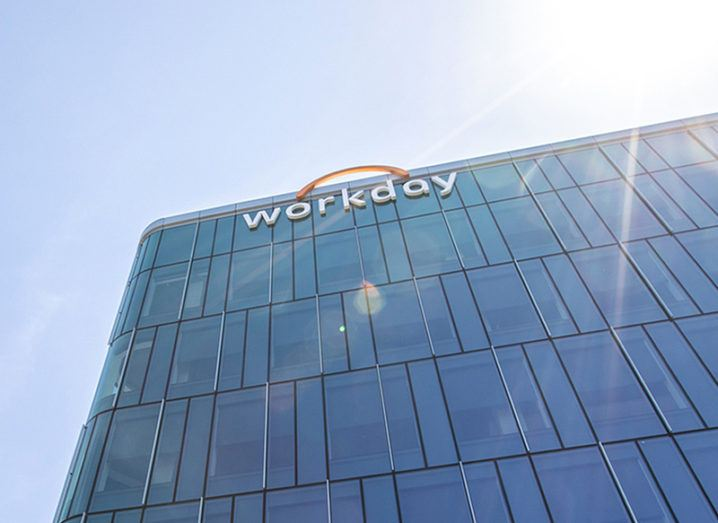 Looking up at a tall, glass-fronted building bearing the Workday logo across the top floor.