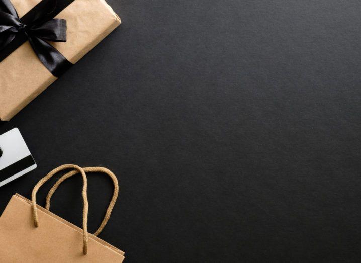 Black Friday sale concept. Frame made of gift box, credit card, shopping bag over black background.