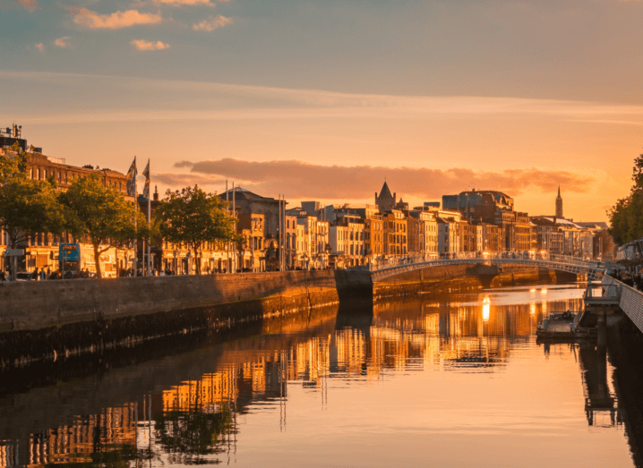 Dublin city in Ireland, as the sun sets over the Liffey river. The Ha'penny Bridge is visible in the background. The water is still and clearly reflecting the buildings on either site of the quays.