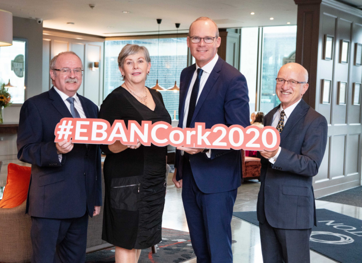 A man in a navy suit with grey hair stands next to a woman in a black dress with grey hair. To her right, there are two more men in navy suits with grey hair. They are all holding up a sign that reads 'EBAN Cork 2020'.