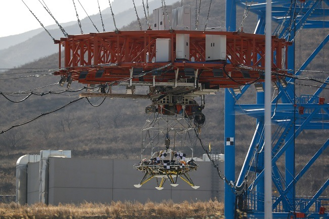 The lander suspended in mid-air by a red lifer beside a blue metal structure.