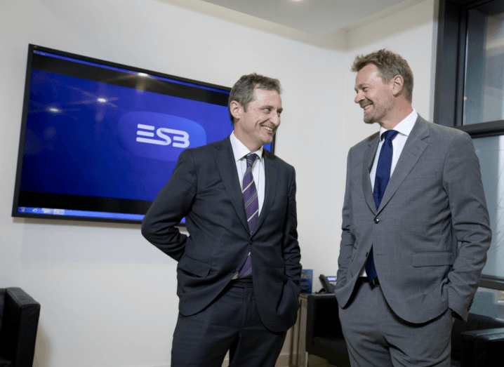 Two men in a grey suits stand beside each other smiling in front of a black TV screen with the ESB logo displayed on it.