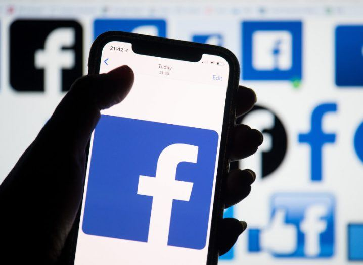 View of silhouette of hand holding phone lit up with Facebook logo.