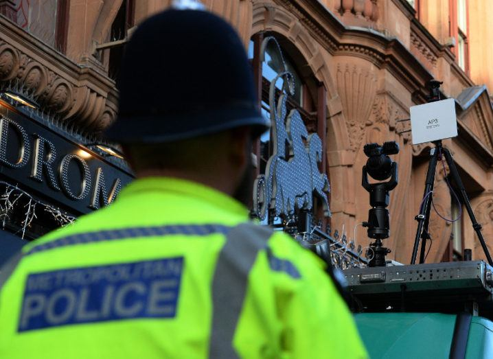 View of UK police officer in high-vis and black hat looking at facial recognition technology.