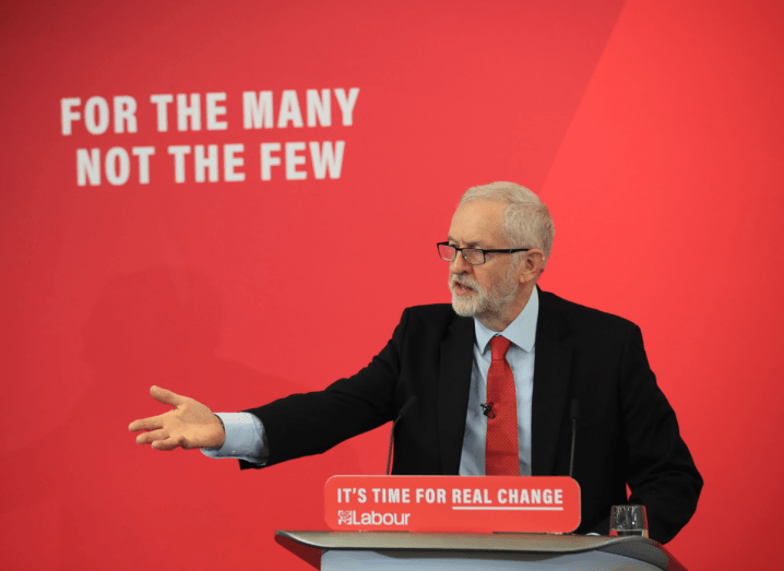 """Jeremy Corbyn, a man with white hair and a white beard, stands in front of a red wall that says """"For the many, not the few."""" He is speaking at a podium, wearing a black suit with a white shirt and red tie. He has his right arm outstretched to the audience."""