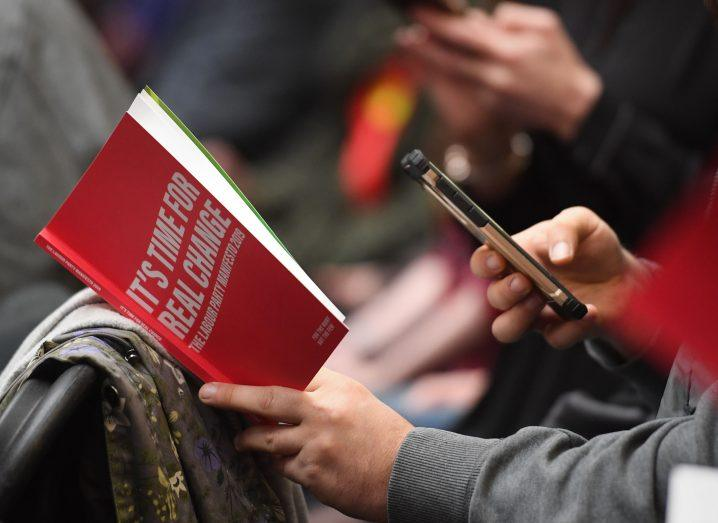 View of Labour Party manifesto in hands of person in grey shirt.