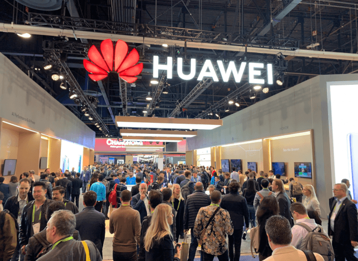 The Huawei logo displayed in lights at a technology event. Underneath the sign, there are dozens of people walking around an exhibition hall.