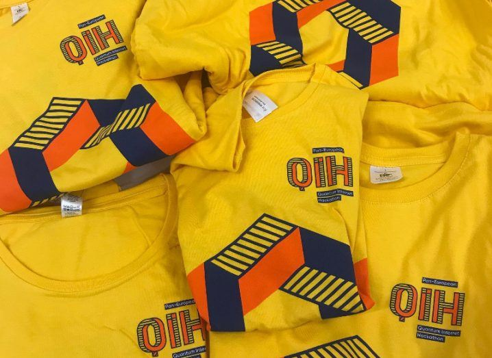 A pile of yellow T-shirts with a graphic 'QIH' emblazoned on them.