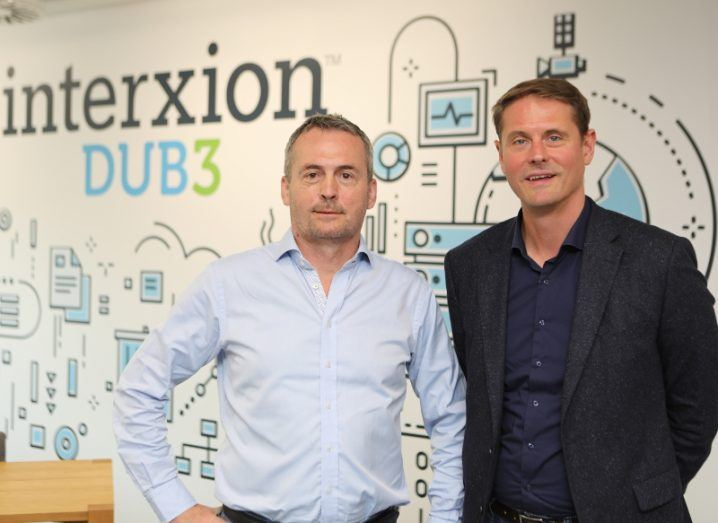 View of two men in business attire standing against mural emblazoned with Interxion logo.