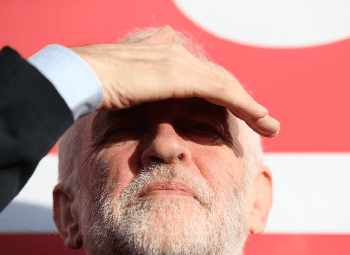 A man with white hair and a white beard covers his brow to see better in a bright light. He is wearing a black suit and white shirt and standing in front of a red sign.