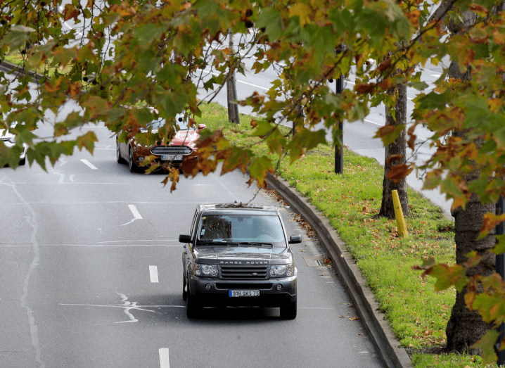 A black Range Rover car driving down a road under a tree with orange and brown autumn leaves.