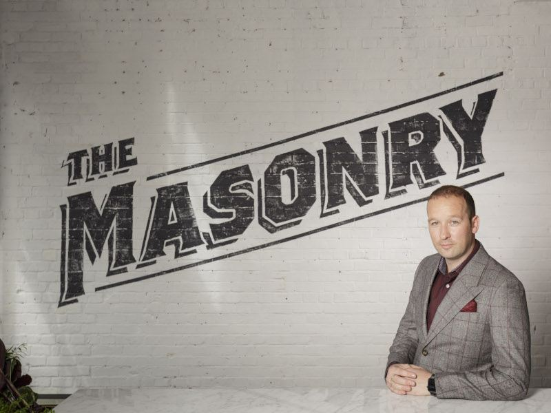 A man in a grey suit stands in front of a wall that reads, 'The Masonry'.