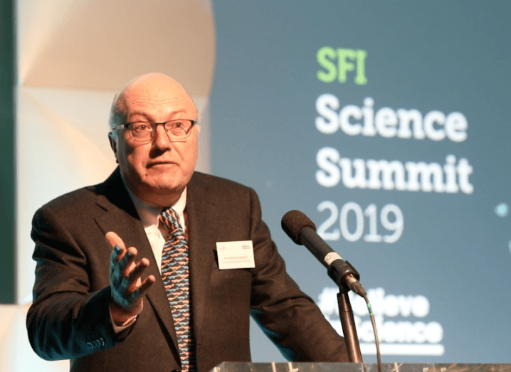 A bald man in a suit and tie stands in front of a microphone on a podium. Behind him is a screen that reads 'SFI Science Summit 2019'.