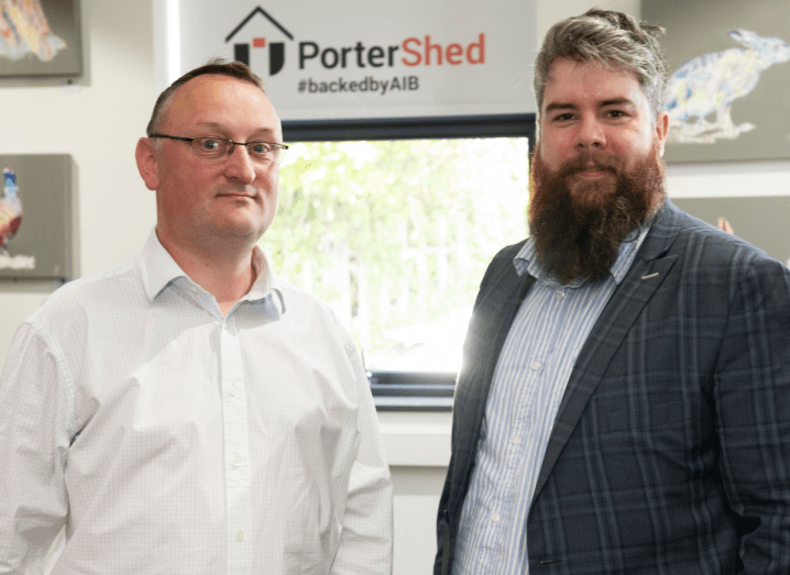 A man in a white shirt with short black hair and glasses stands beside a bearded man in a grey suit jacket and blue shirt. They are standing in front of a window, which has a sign saying PorterShed on it.