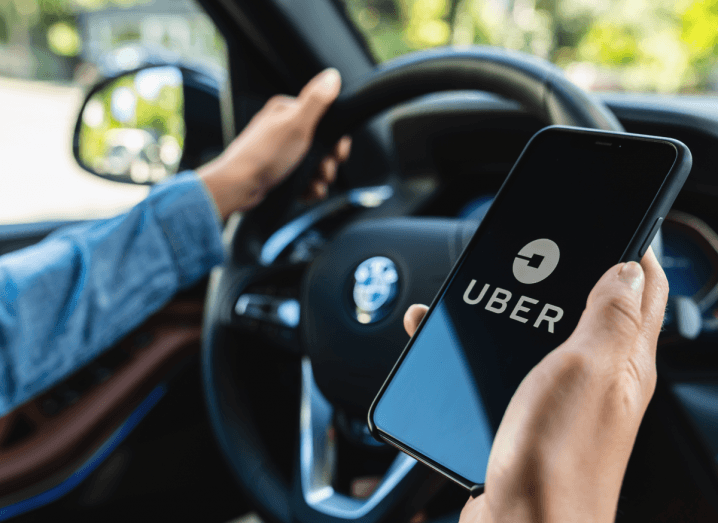 A driver in a blue denim shirt's arms are visible holding the steering wheel of a BMW in his left hand and holding an iPhone with the Uber logo displayed on screen in his right hand. The view outside of the car's window is blurred but it appears to be a sunny day and the driver is beside trees with green leaves.