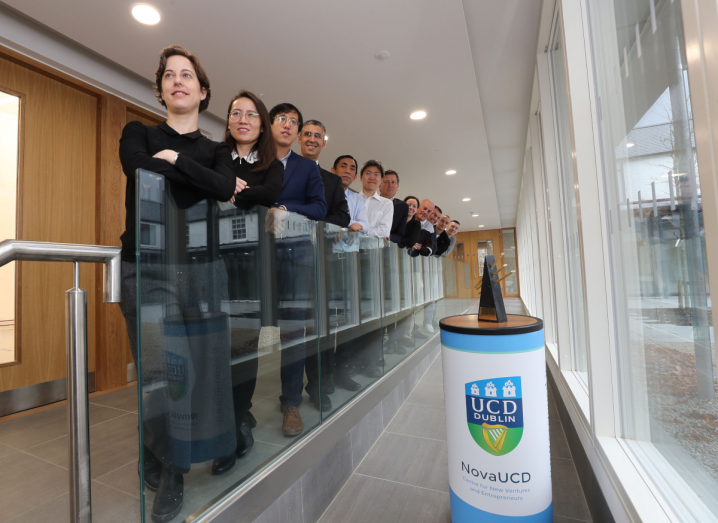 A row of people standing against a glass banister in UCD, posing for a photograph. Beside them is a small podium with the UCD logo on it.