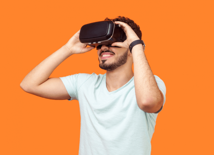 A man in a white T-shirt using a VR headset in front of a bright orange background.