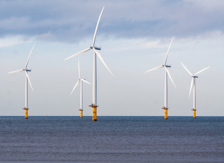 Wind turbines on a sea under a cloudy sky.