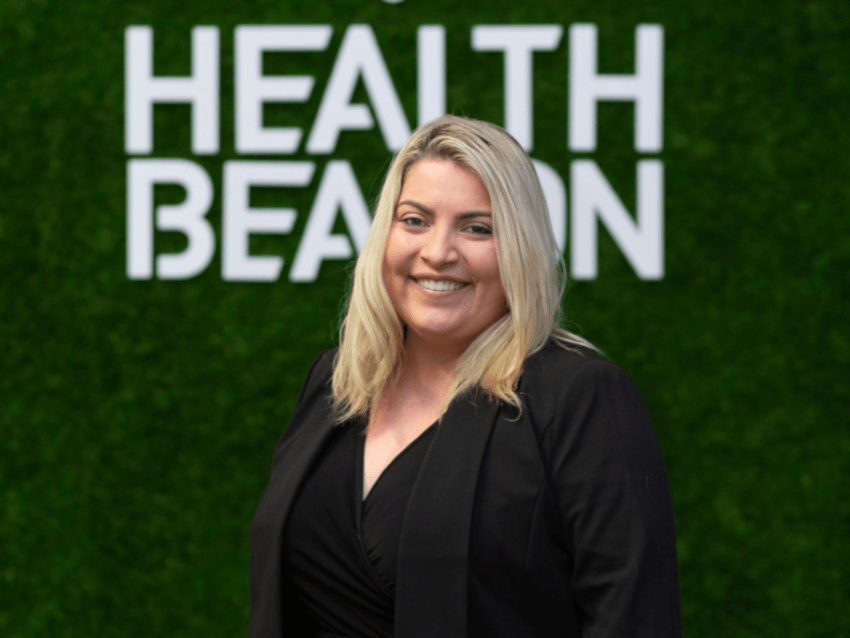 A woman with blonde hair wearing a black blazer and black top underneath stands in front of a green wall that reads HealthBeacon.