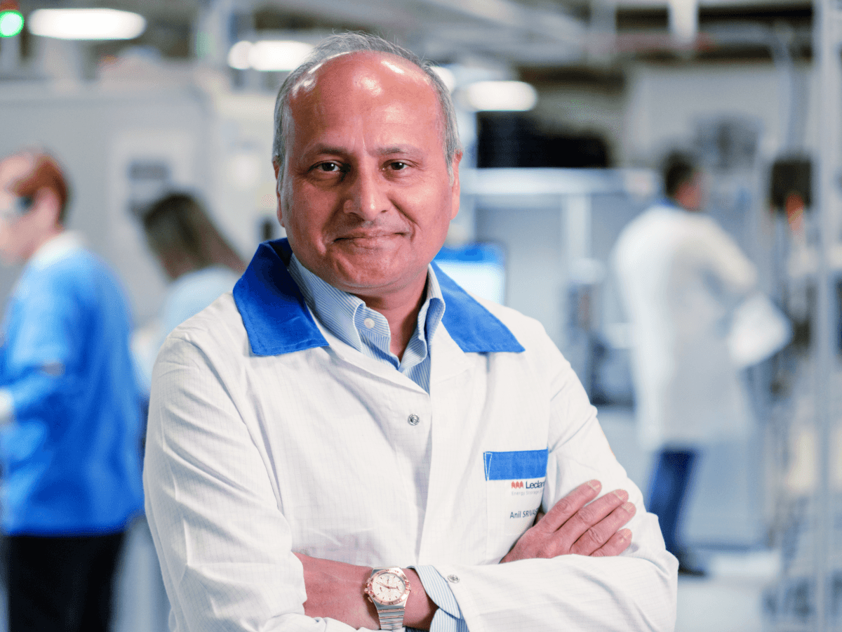 A man in a white lab coat stands with his arms crossed in a room that appears to be designed for manufacturing.
