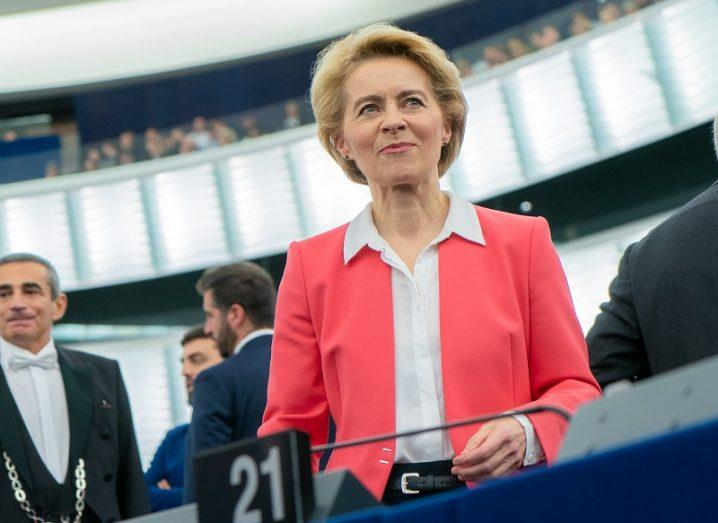 Ursula von der Leyen in a pink blazer smiling in the EU Parliament chamber.