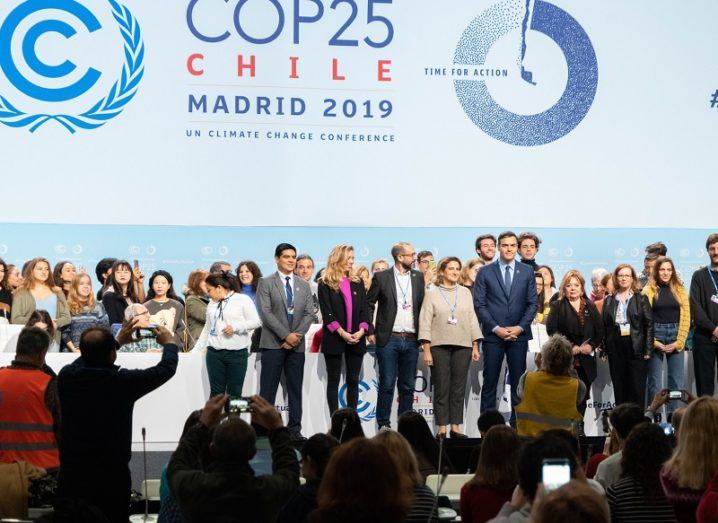 Delegates standing on stage in front of camera crews at COP25 in Madrid.