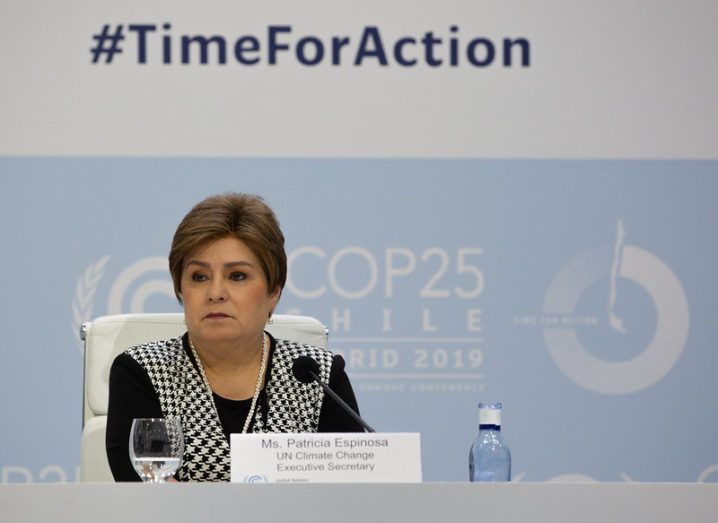 A woman in a houndstooth-patterned cardigan is seated at a panel under a backdrop bearing the slogan '#TimeForAction'.